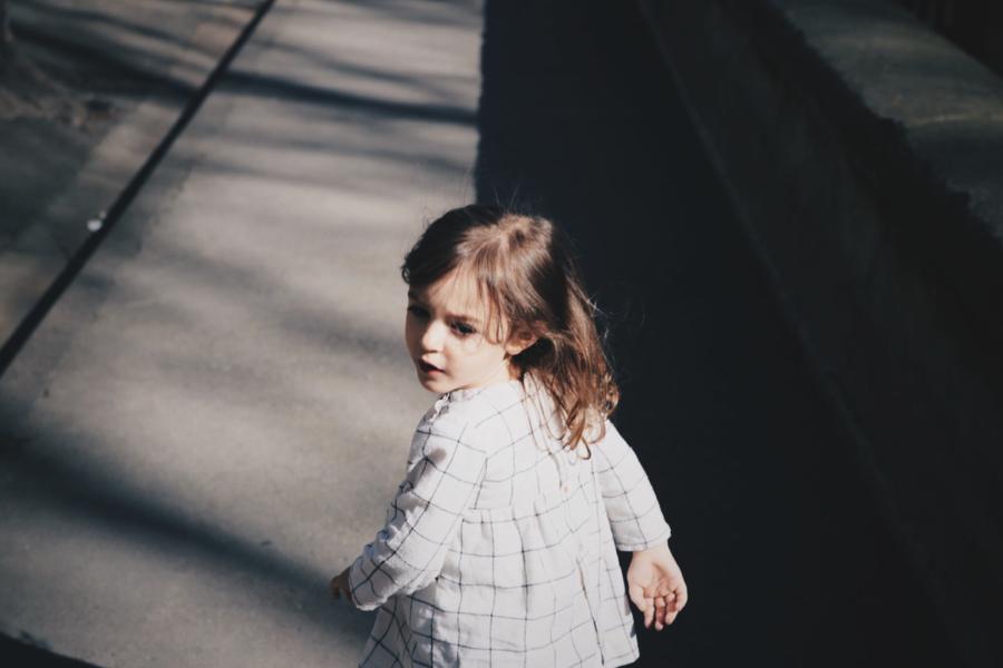Young girl running down sidewalk